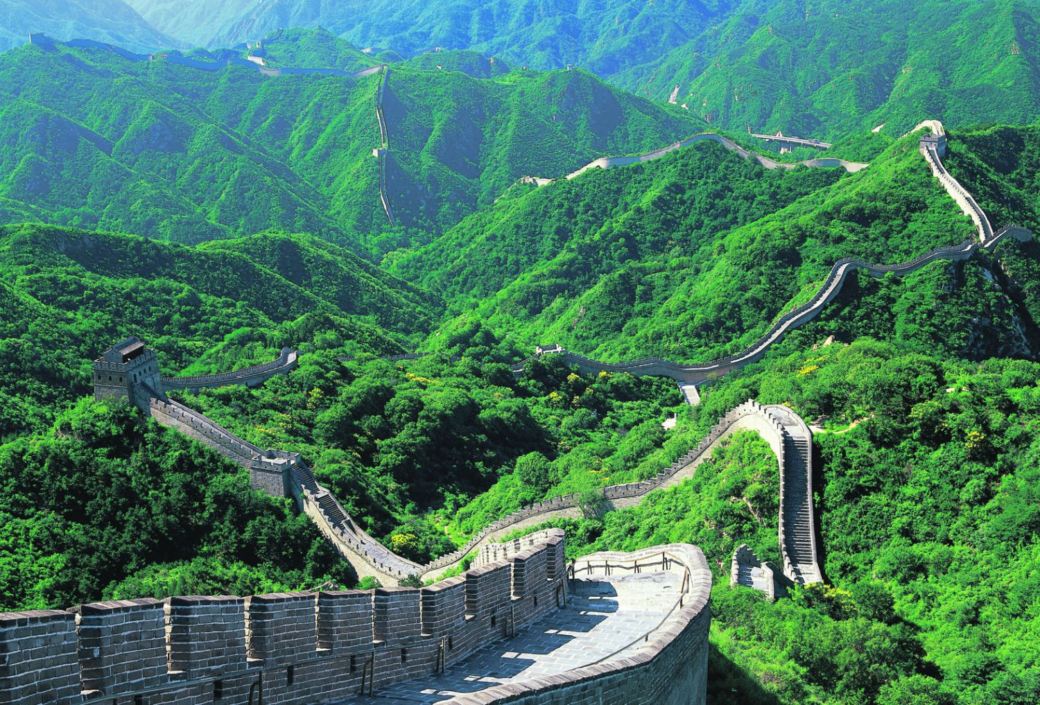 The Great Wall of China on a green mountainous landscape