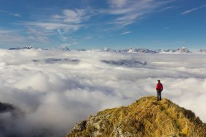 Man on a peak above the clouds